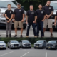 Group of people standing in front of cars